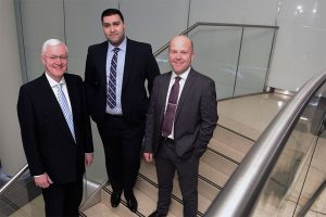 3 men in suits smiling and stood on some stairs in an office building