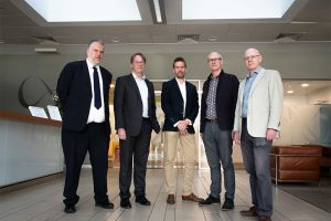 5 men in suits smiling and stood in the reception area of an office