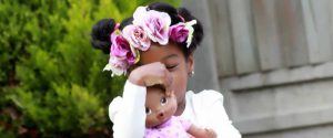 A young girl with flowers in her hair holding a doll