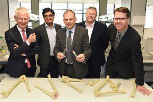 5 men in suits stood around a table of plastic bones