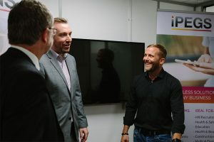 3 men having a conversation in a meeting room with a TV screen on the wall and and iPEGS pop up banner in the background