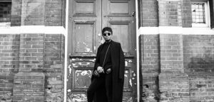 A man dressed in black with sunglasses posing outside of an old building