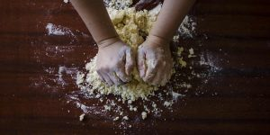 A close up of hands kneading dough on a worktop