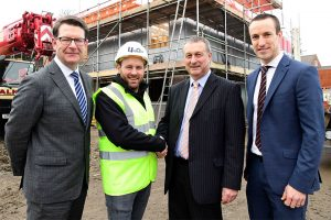 3 men in suits and one man in a Hi - Vis jacket stood in front of a construction site