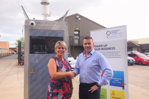 A man and a women shaking hands in a car park with surveillance equipment and a MEIF pop up banner behind them