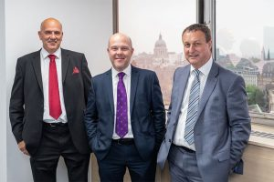 3 men in suits smiling and stood in a meeting room with the city of London in the background