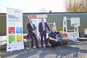 3 men stood outdoors near some trailer equipment with a Midlands Engine Investment Fund pop-up banner next to them