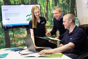 2 men and a woman in a meeting room with a tree themed feature wall looking at a brochure and a laptop