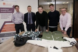 5 men from Oneskee stood in a meeting room with snow sports apparel on the table in front of them
