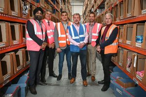 A group of employees from the Online Poundshop wearing Hi Vis vests in a warehouse