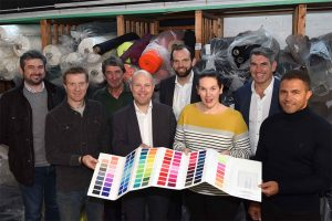 Employees from Proskins holding a colour swatch book with rolls of fabric in the background