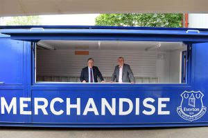 2 men in suits stood in a Everton Football Club branded pop-up shop