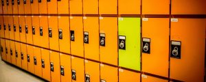 A row of orange lockers with one yellow locker in between