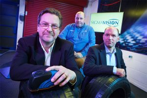 Three men from Sigma Vision sat in an office with some tyres