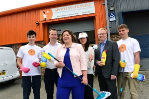 Employees from Spotless Cleaning holding a variety of cleaning products