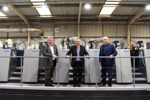 Three men in suits from Streamline Press stood in front of commercial printers