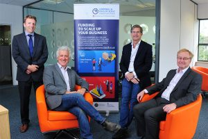 Four men in suits in a Swoop Applications office with a Cornwall and Isles of Scilly Investment Fund banner