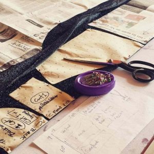 A selection of sewing equipment including scissors, pins, fabric and sewing patterns