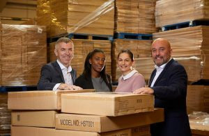 Four employees from Total Racking Solutions standing in between brown boxes