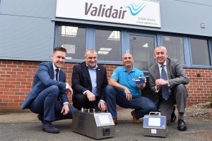 Four men kneeling in front of the Validair office showing their environmental monitoring equipment