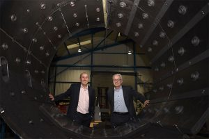 Two men in suits standing behind a vacuum furnace