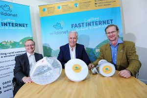 Three men sat at a table showing their broadband product called Wildanet