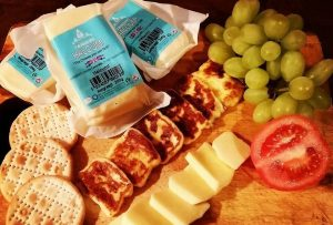 A cheeseboard with a selection of cheese, crackers, tomatoes and grapes
