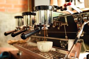 A coffee machine pouring coffee into a white mug