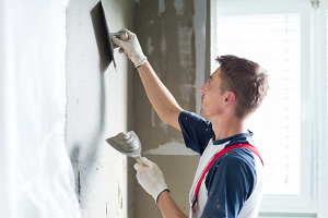 Plasterer renovating indoor walls and ceilings with float and plaster