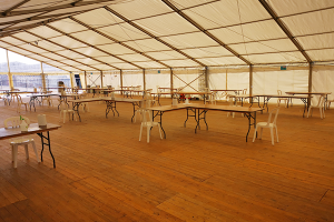 A marquee with tables and chairs and a wooden floor