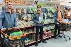 Members of staff in one of Pet Place's stores, posing for the camera and holding items available in store