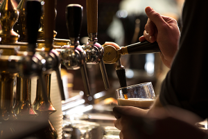 Closeup of a bartender pouring a dark stout beer in tap
