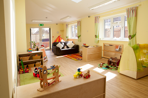 Baby room at Little Adventurers nursery, featuring furniture, wooden toys and little play areas
