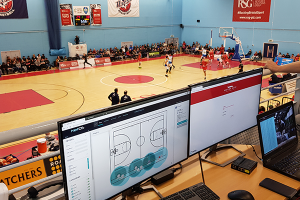 Zeetta Networks software on computer monitors with a n indoor basketball court in the background