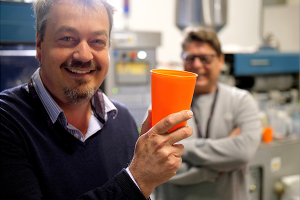 Bockatech CEO holding up a plastic moulded product to the camera, with one of his technician colleagues in the background