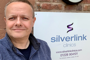 CEO of Silverlink Clinics standing beside his company's nameplate fixed to the exterior of the clinic