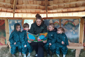 A member of nursery staff reading a book to four children, under the roof of a sheltered outdoor play area