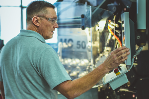 A Hanson Springs employee operating a manufacturing machine on their premises