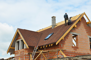 Builders working on constructing a roof on a new build home