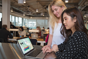 Two young women looking at a laptop displaying Machinelabs software interface