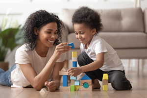A female nanny and a young boy stacking blocks to make a tower