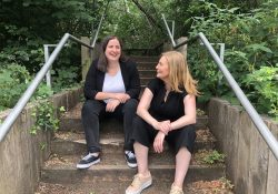 Two female founders of Organise sat on steps outdoors