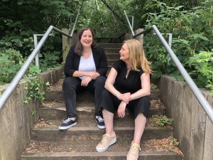 Organise founders founders Bex Hay and Nat Whalley sitting on some outdoor steps