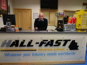 Malcolm Hall MBE, managing director of Hall-Fast Industrial Supplies, standing behind the counter at his company's store