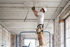 Electrical contractor drilling a concrete ceiling