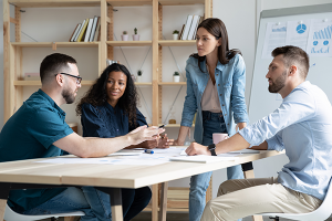 Four young colleagues having a marketing meeting around a desk in a modern office