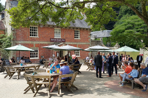 Exterior of the Spread Eagle Inn, with groups of people sat at outdoor tables drinking and eating