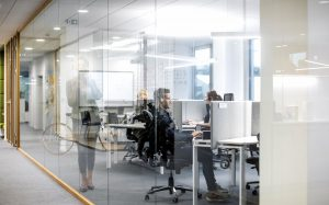 Interior of modern offices, with employees at desks wearing headsets and holding phone conversations with clients