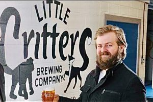Matt Steer, MD of Little Critters Brewing Company, standing outside his brewery, holding a tankard of ale