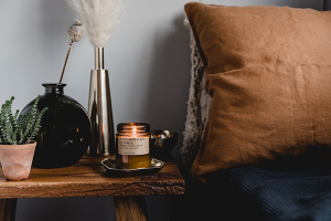 One of Osmology's range of scented candles placed on a bedside table